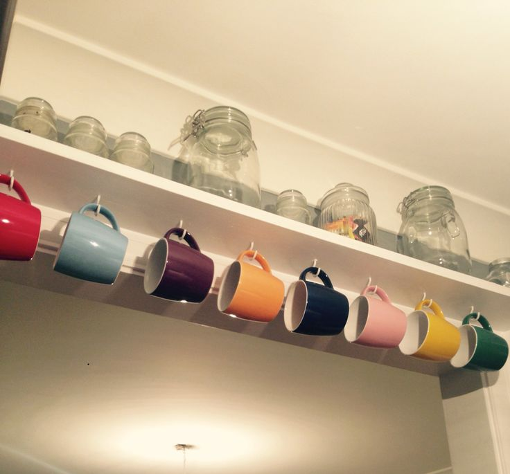 Kitchen shelf with multicoloured mugs hanging from it. Kitchen idea. Extra storage.