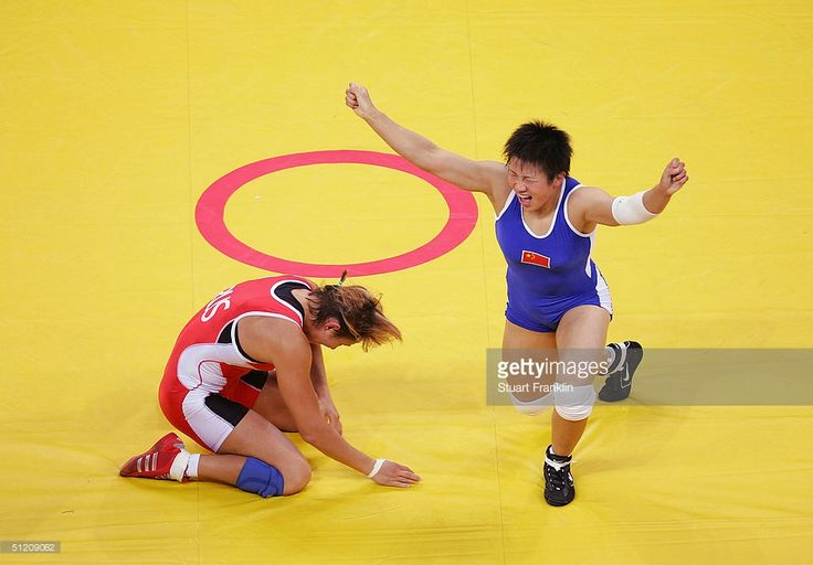 Xu Wang (blue) of China celebrates beating Gouzel Maniourova of Russia in the women's Freestyle wrestling 72 kg gold medal match on August 23, 2004 during the Athens 2004 Summer Olympic Games at Ano Liossia Olympic Hall in Athens, Greece.