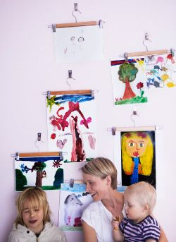 Hanging art Kids love to draw and they get so much out of displaying their work. For those fan-favorites in constant rotation, skirt hangers make great quick-change frames.