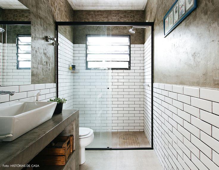 Banheiro tem meia parede revestida com subway tiles e meia parede de cimento queimado.