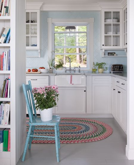 ***** white country cottage kitchen with mix glass door and closed cabinets, useful narrow undershelf, farmhouse sink w/ high bridge faucet, grey counter, pale blue tile set in diamond pattern, painted wood floor, design by Les Ensembliers, Canada