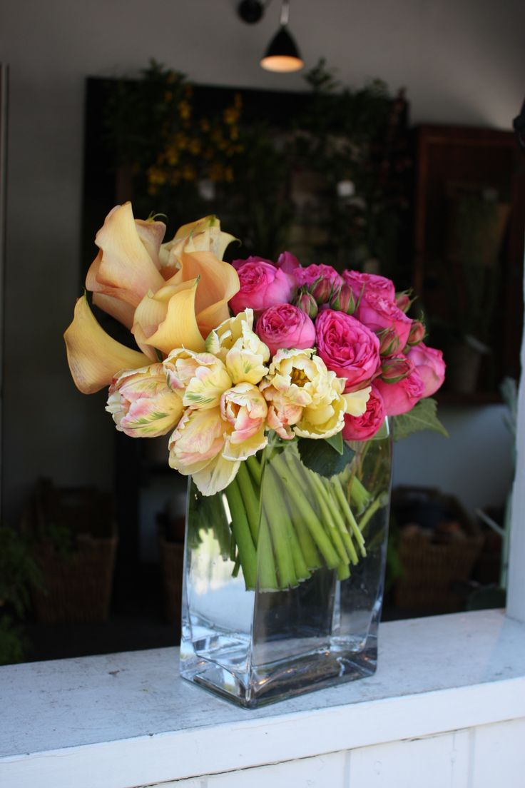 A modern mix of peach calla lillies, yellow parrot tulips and pink garden roses cleanly arranged by Botany Flowers