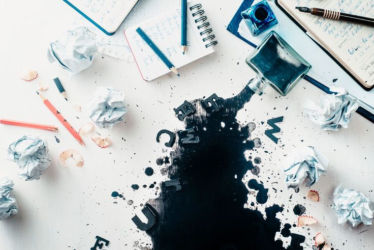 Writer workplace with spilled ink, crumpled paper, scattered letters, papers and notepads on a... - Writer workplace with spilled ink, crumpled paper, scattered letters, papers and notepads on a white wooden background. Header with creative writing concept. Flat lay with copy space. High contrast still life.