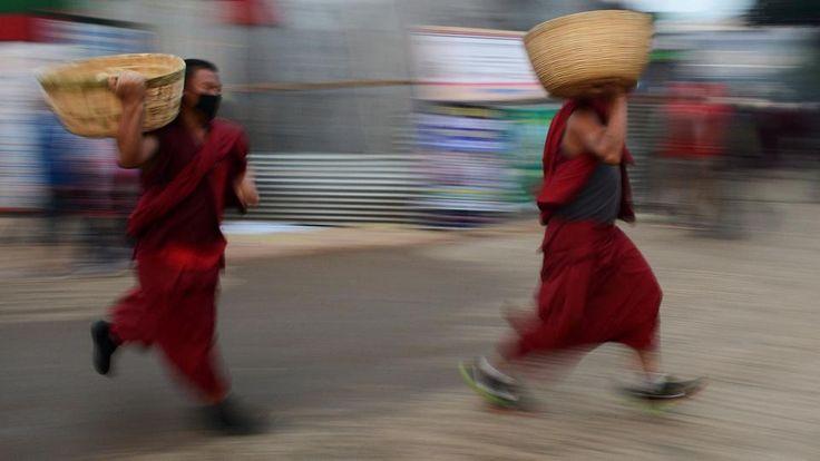 Buddhistische Mönche rennen mit Brotkörben durch die indische Stadt Bodhgaya. Sie wollen die Teilnehmer an einem Gebet des Dalai Lama versorgen. | Bildquelle: AFP