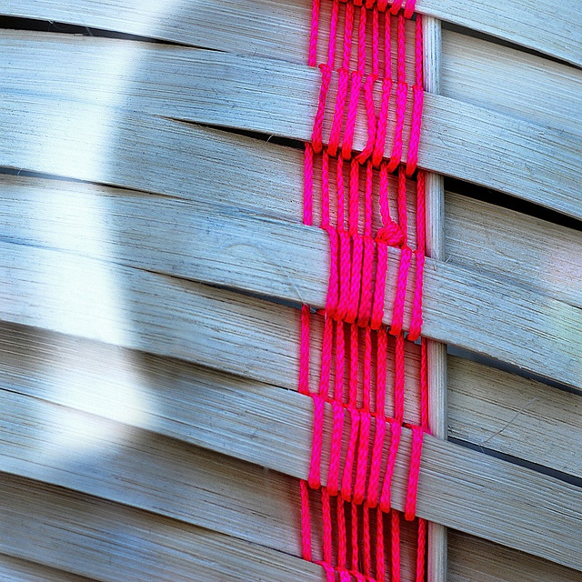 Neon weaving on wood.