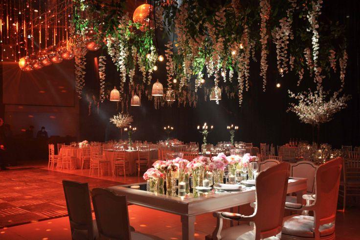 Mesa principal de estilo con tapa de espejo, sillas estilo Luis XV, floreros calados en tonos pastel. Desde el techo glicinas blancas y bombitas de luz dimerizadas. by Mercedes Courreges Ambientaciones