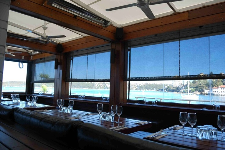 Motorised retracting shade and also clear pvc side screens at Hugo's, Manly, block the westerly sun, wind and rain.