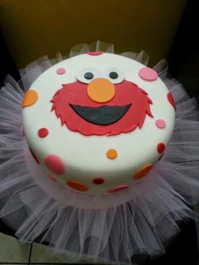 Elmo birthday cake for girls complete with tulle and pink polka dots.  See more Elmo birthday party ideas at www.one-stop-party-ideas.com