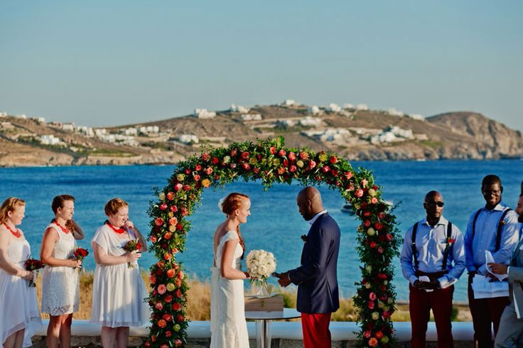 A colourful arch filled with red and orange roses to exchange their vows, overlooking the Aegean blue.
