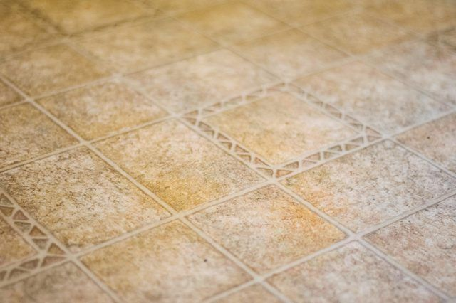Linoleum bathroom floors are durable and relatively inexpensive. The floors also resist stains, but they are prone to discoloration from rubber. Rugs that contain a rubber backing will leave behind yellow stains that will make the linoleum floor look unpleasant due to the antioxidants in the rubber material reacting with the plastic in the...