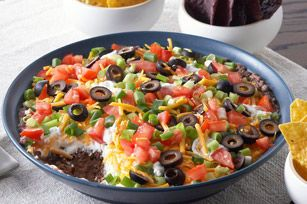 This easy appetizer takes only 10 minutes to prep. Topped with sour cream, cheese and chopped veggies, this Mexican bean dip pairs perfectly with crunchy tortilla chips.