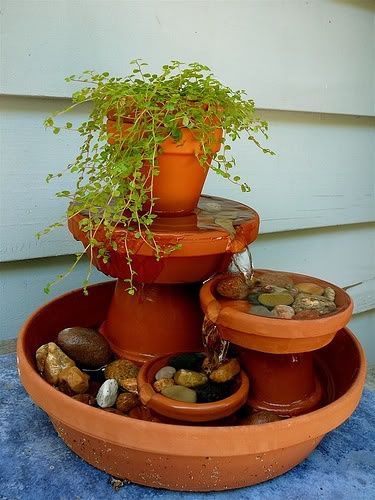Hm? Lovely small fountain of terracotta pots! IWould attract birds and (if the stones break the water surface) butterflies. -- Put fountain equipment under bottom pot of tallest part, and run tubing up to top saucer. Looks like you need to cut an opening in each saucer for directed spillover.