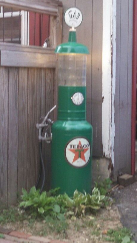 Repurposed air compressor tank, 5 gal. pail, 5 gal. water bottle, lamp shade. A light inside the pail shines through the bottle.