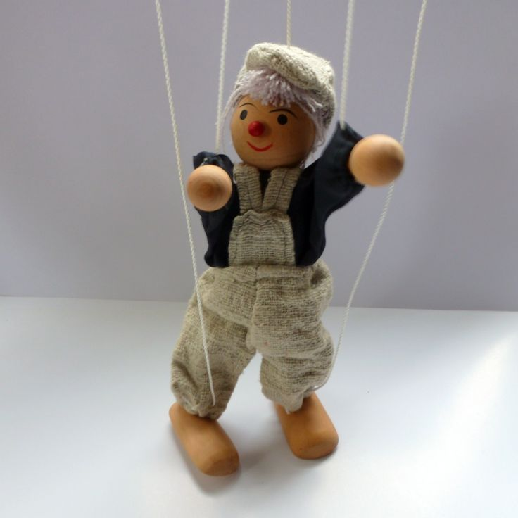 Found at an auction house in Great Britain, this happy little chap would look lovely hanging in a child's room.We have no idea of his age or origin, but are sure that kids will adore his cute wooden face.Handpainted features, wooden head, feet and hands. Wearing a brown shirt and matching sage cap and dungarees. The puppet is in very good condition, all the strings are there and the wooden cross to which they are attached will make it very easy to hang up high.A sweet decorative piece, not…