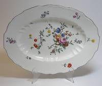 Ovale, leicht gemuldete Platte, Carl-Theodor-Marke 1762-1794. Im Spiegel und auf der Fahne farbige Blumen- und Früchte-Malerei. Bewegter Rand braun staffiert, Altersspuren, keine Bestoßungen. Länge: ca. 37 cm.