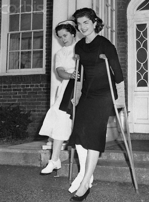 Mrs. Jacqueline Kennedy, wife of Senator John F. Kennedy (D.-Mass.), is assisted by nurse Shirley Goodall as she leaves New England Baptist Hospital. Jacqueline, who broke her right ankle while playing touch football at the Cape Cod home of her father-in-law, former U.S. Ambassador to Britain Joseph P. Kennedy, expects to be wearing a cast for six weeks (November 18, 1955) (Photo Randy Faris/Corbis)