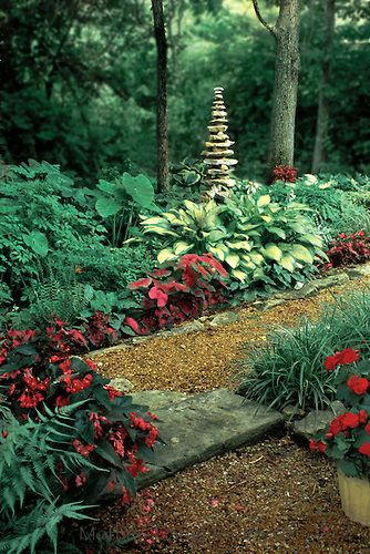 Tall cairn in shade garden surrounded by hostas, begonias, ferns and impatiens.