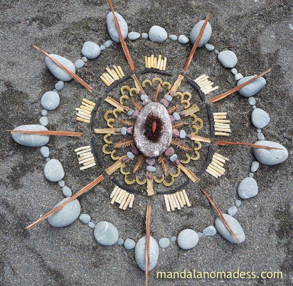 Mandala Art Medium: ~~dried bull kelp bulb, feathery red seaweed, red/white rock, dried fern leaves, bull kelp, red rock, grey stone, black seaweed stipe, bleached seaweed rope, eucalyptus bark on dark sand canvas~~
