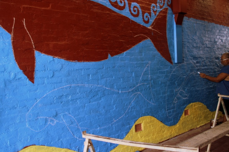This is a  25 metre mural about dugongs being painted by a Torres Strait Island artist in Cairns Queensland Australia.