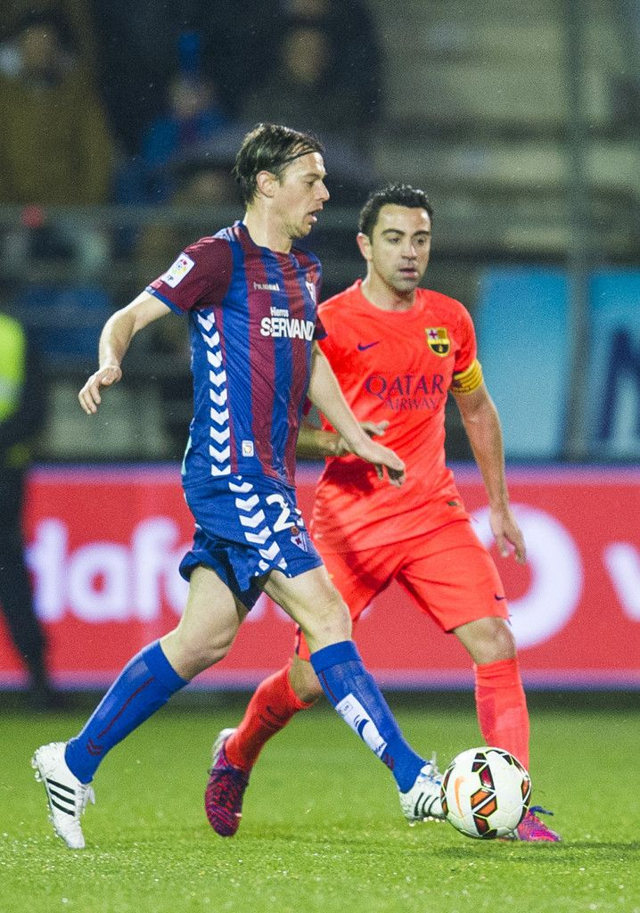Xavi Hernandez of FC Barcelona duels for the ball with Javier Lara of SD Eibar during the La Liga match between SD Eibar and FC Barcelona at Ipurua Municipal Stadium on March 14, 2015 in Eibar, Spain.