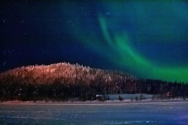 Revontulten leikki. Northern lights behind the lake Immeljärvi.
