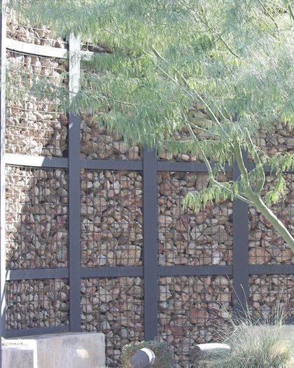 these eco mesh panels were filled with rocks to create a rock wall partition - Rock Wall Design