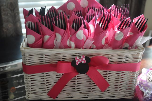 Buy basket, tie ribbon in front, wrap forks in pink and white polka dot napkins and make a mini mouse centerpiece for the ribbon.