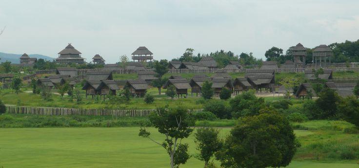 reconstitution Yoshinogari_Ancient_Ruins_  Probablement issue de groupes d'émigrants venus de la Corée et de Chine, cette civilisation apporte les rizières inondées, l'usage du fer et l'établissement de véritables royaumes organisés.   Les maisons sont surélevées, avec des murs en terre battue et des toits en chaume. Elles se regroupent en villages importants protégés par des fossés.
