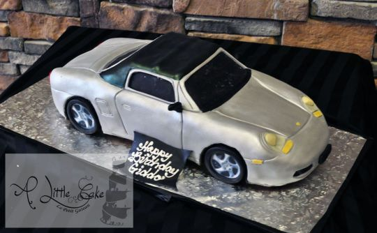This birthday cake is innovatively designed to resemble a classic sports car – Porsche.