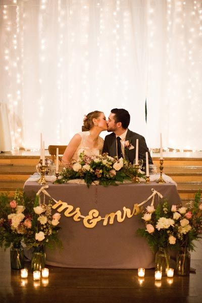 Set a romantic sweetheart table with beautiful flower arrangements and a twinkling backdrop.