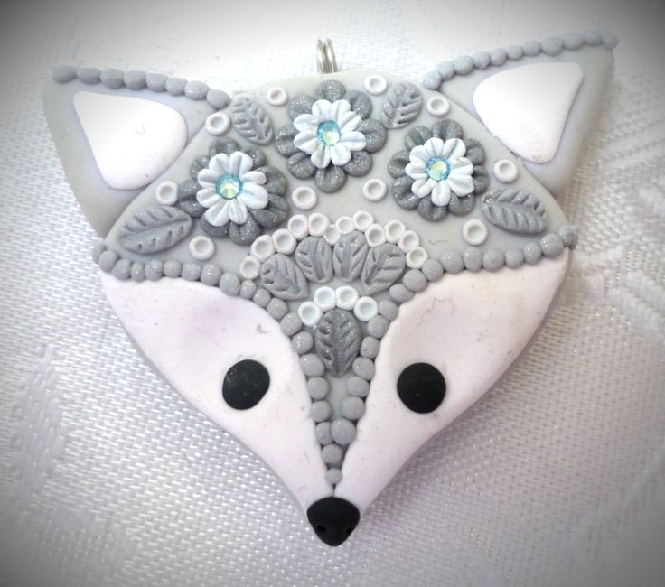 Polymer clay Fox pendant, handmade with applique technique, one of a kind. Light gray with white, black eyes and nose, with lacy decoration of flowers, leaves and dots in various shades of silver and a light blue crystals. By Lis Shteindel.