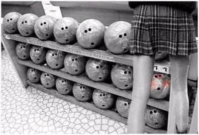 Ogling bowling balls. (Holy moly, those are some skinny legs.)