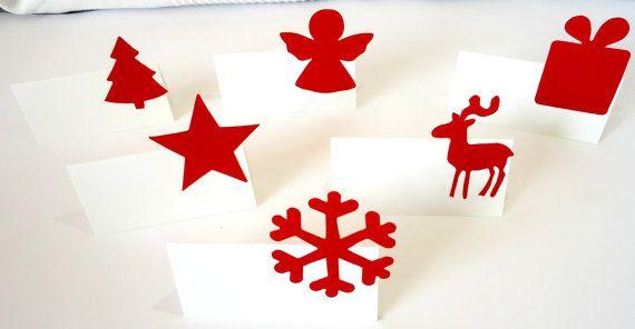 Set de 6 marque-places blancs décorés de formes de Noël rouges.  Cest un set très simple pour agrémenter votre table de Noël. Les cartes