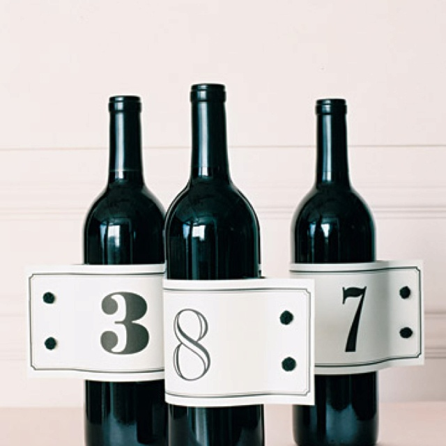 Wine bottles with cuff link number tags...Rehearsal dinner by the groom's cake?