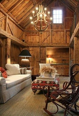 Textured old wood sets the tone in the great room of this converted barn home. A twig rocker and chandelier made of wine barrel staves keeps the interiors authentic for the setting.