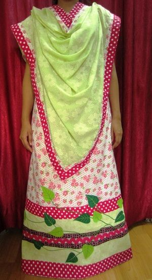 White cotton fabric with floral and polka dot print designed into a beautiful lehenga inspired by a 'Money' plant.  Contrast color lime green voile dupatta used insync with the leaves made of felt along with tape lace, panels and trims.