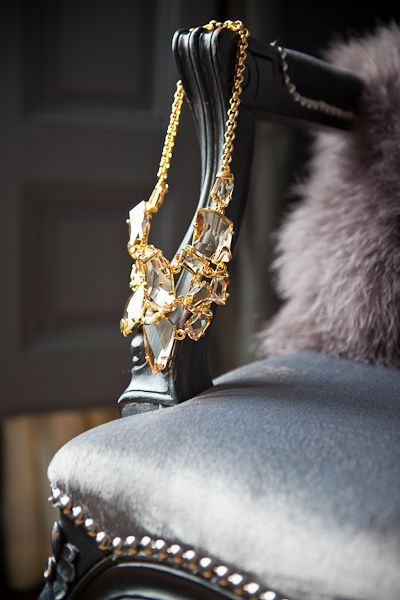 A gorgeous statement necklace hangs off the arm of a fur clad chair with satin upholstery and silver studs. J'adore!