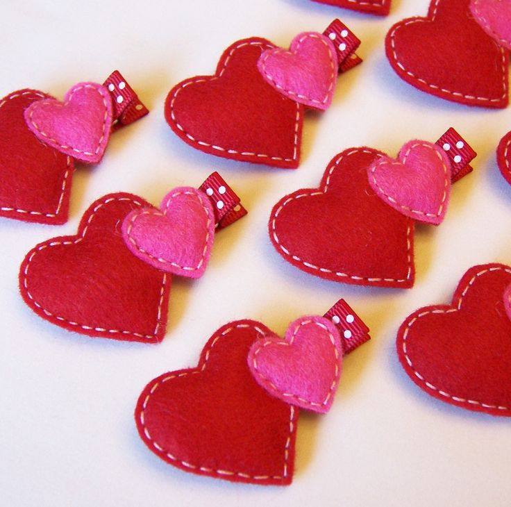 """double heart felt embellishment measures approximately 2"""" wide and 1 1/2"""" long and is mounted on an alligator clip that measures 1 3/4"""" long. The clip is partially lined with 3/8"""" premium polka dot grosgrain ribbon. All of the ribbon ends have been heat treated to prevent fraying."""