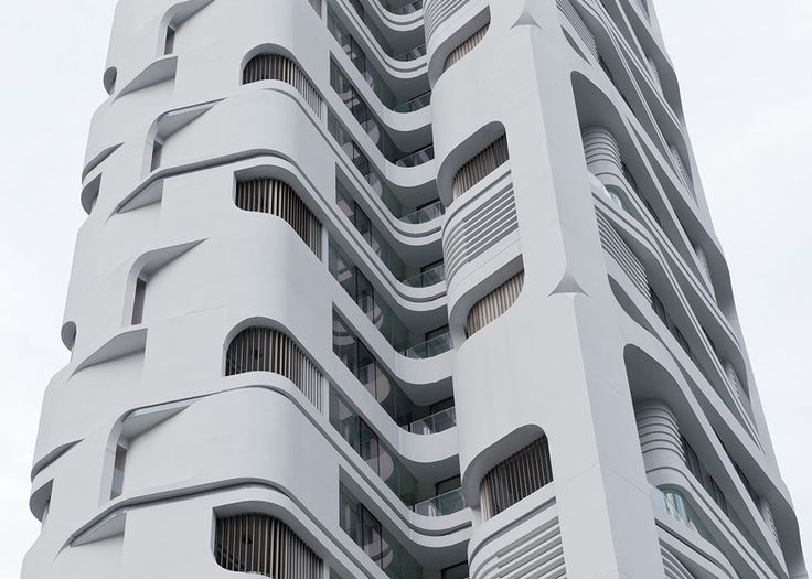 An elaborate facade comprising curved edges, deep recesses and sliced windows wraps this 135-metre skyscraper by Dutch office UNStudio in Singapore .