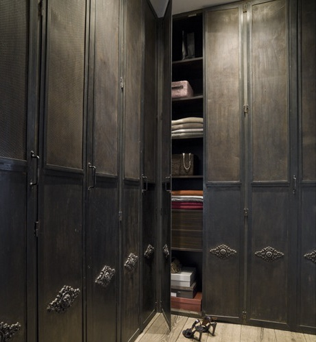 I love the antique steel doors on the wardrobe. I would hang crystal chandelier in the middle or something with colorful glass to add a feminine touch.