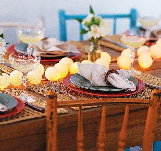 Não quer usar velas? Eis uma alternativa vapt-vupt para um efeito luminoso no jantar: espalhe um cordão de luzinhas com bolas ao longo da mesa. A ideia funciona melhor se o móvel estiver próximo a uma parede com tomada