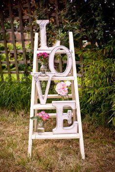 LOVE this vintage display piece made with white ladder, pink flowers, clear jars, and huge letters.