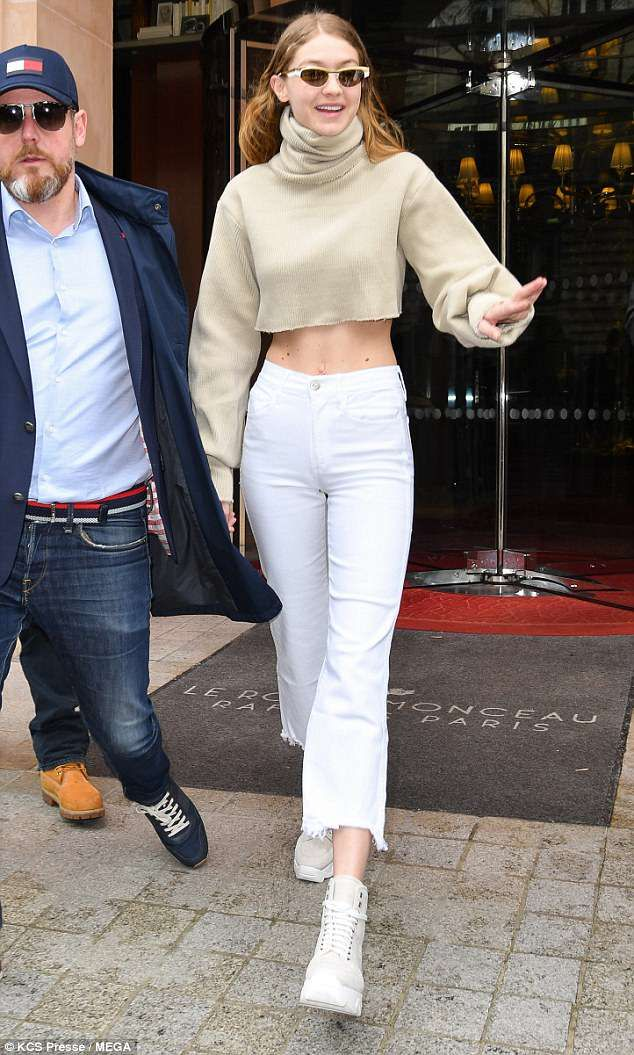 a1aef4ee A bit of all-white: She teamed the jumper with bright white jeans adorned  with a rugged fr... #gigihadid