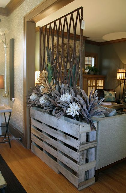 Room divider made from a pallet and iron panel;  Radiator drip tray as planter base filled with rocks.