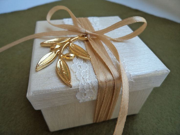 Off white favour box decorated with beige satin ribbon and a gold metallic olive leaf.