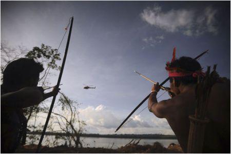 Habitantes de las aldeas cercanas a Altamira, en el norte de Brasil, dirigen sus flechas a un helicóptero de la policía que sobrevuela la zona. Esta región había sido ocupada por alrededor de 300 activistas, indígenas, pescadores y residentes de los asentamientos costeros, que protestaban contra la construcción de centrales hidroeléctricas. Fotografía Lunae Parracho.