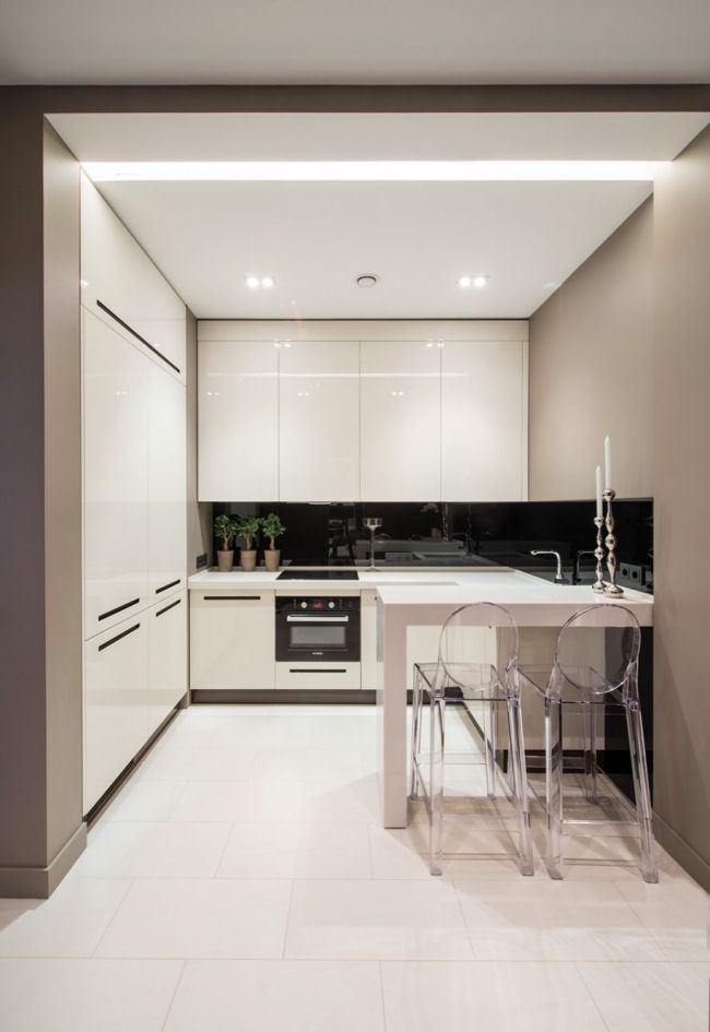 Tiny small compact white kitchen with floor to ceiling cupboards and black splashback in architecture interior design