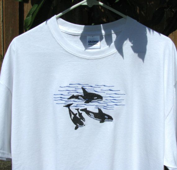 These are Custom Order T-Shirts designed to be worn by men or women. Please choose your size and color from the drop down menus. They will be embroidered to your satisfaction within two weeks or less. Please allow extra time for shipping to you.  This custom Embroidered Orca Whale Pod T-Shirt design was inspired by a trip whale watching in the San Juan Islands. This Embroidered Design depicts several adult orcas and a baby swimming in the Straits of San Juan. We are so happy about this…
