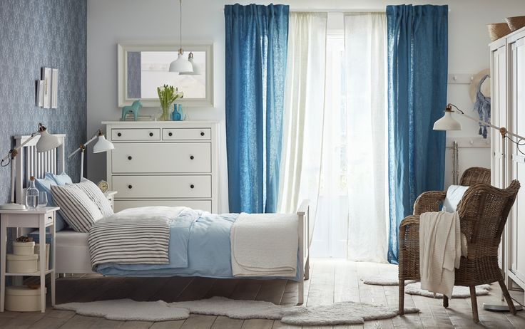 A medium sized bedroom with a white bed for two with bedlinen in light blue and gray. Shown together with a white chest of drawers, mirror and two bedside tables.
