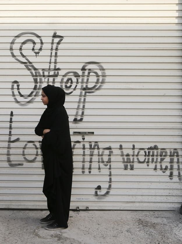 30% of Bahraini women suffer from domestic abuse. A woman's testimony is worth half a man's before Bahrain's Islamic courts.  Pictured here a woman watches the funeral procession for a Bahraini killed by police during anti-government protests. The graffiti references allegations that Bahraini police have tortured women arrested for opposing the regime.